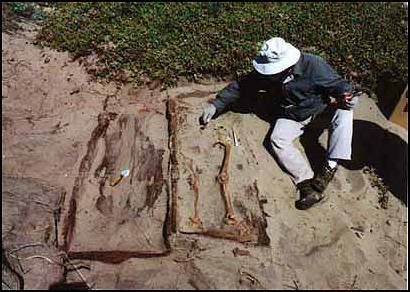 Peter Schulz next to exposed burial sites.