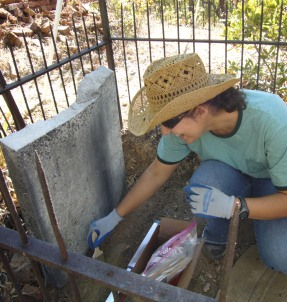Cleaning a grave site at Shasta SHP Catholic Cemetery