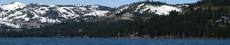 View of Donner Lake shoreline and snow capped mountains at Donner Memorial SHP